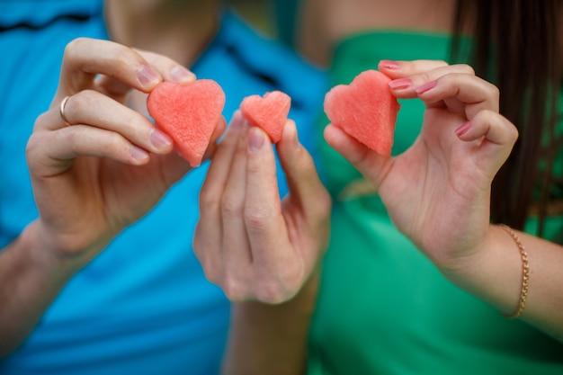 Famille attend un bébé avec des tranches de pastèque en forme de coeur