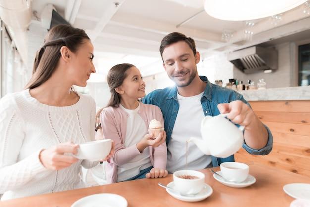 Famille au café papa pours tea kid has cupcake.