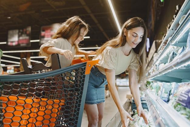 Famille au supermarché. femme dans un t-shirt marron. les gens choisissent les produits. mère avec fille.
