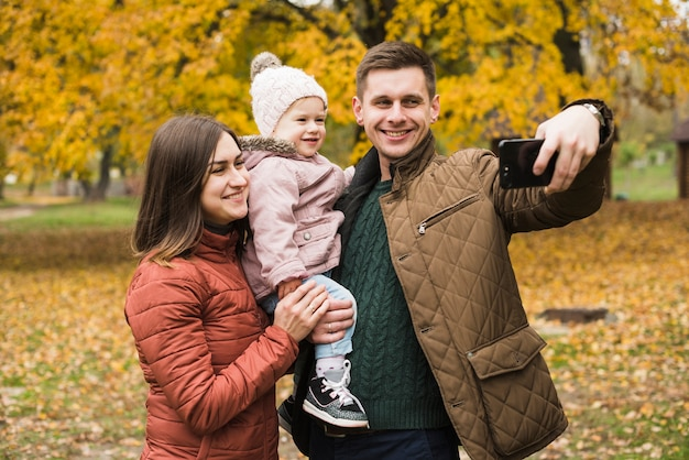 Famille en automne parc faisant selfie