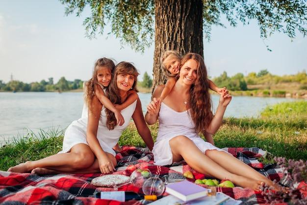 Famille ayant pique-nique au bord de la rivière l'été au coucher du soleil. mère, grand-mère et enfants s'embrassant. trois denerations