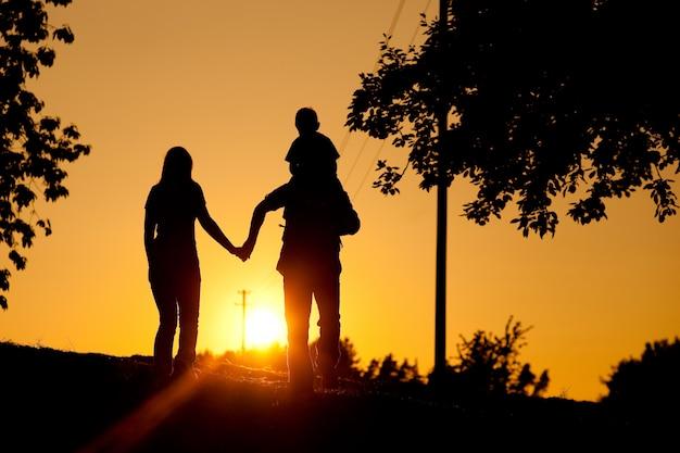 Famille ayant une promenade au coucher du soleil