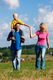 Famille ayant une promenade sur le pré