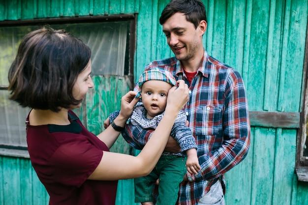 Famille avec bébé debout à l'extérieur de la maison
