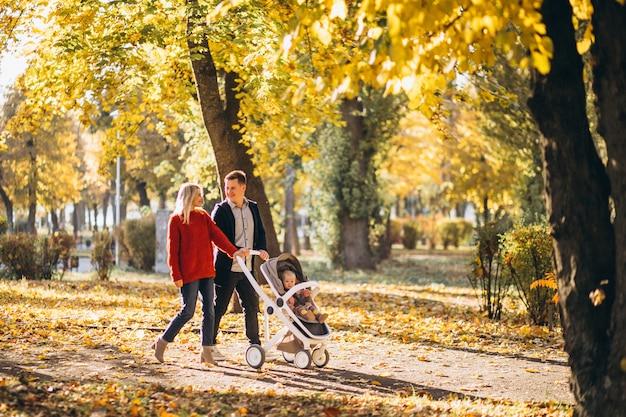 Famille avec bébé fille dans un landau à pied d'un parc en automne