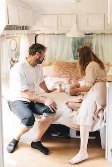 Famille avec bébé sur le lit dans la remorque le matin