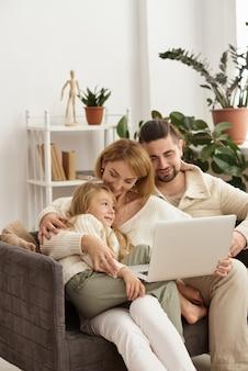 Famille avec bébé à la recherche d'un ordinateur portable