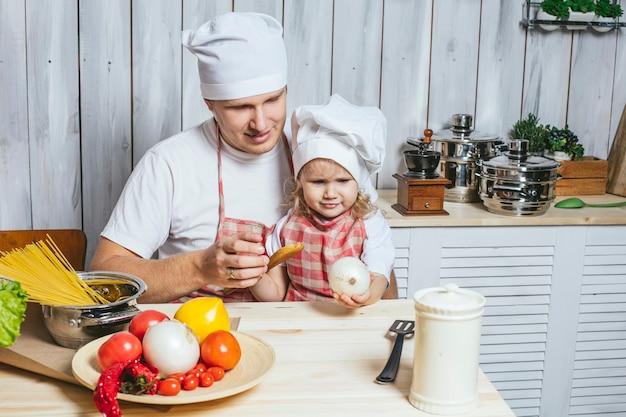 Famille, belle fille papa à la maison la cuisine en riant et en préparant la nourriture ensemble