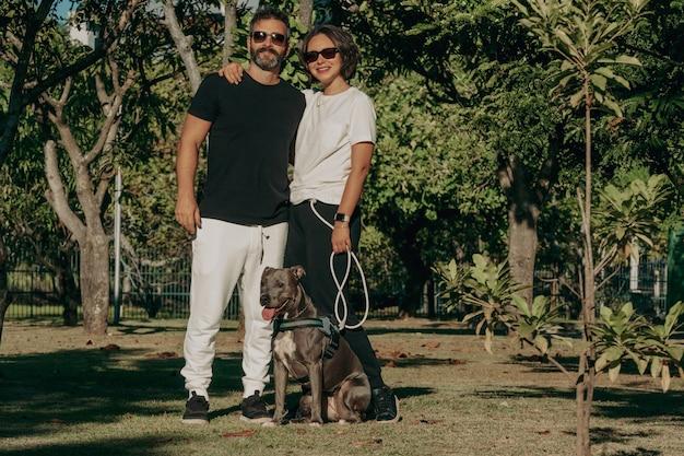 Famille brésilienne formée d'un homme, d'une femme et d'un pit-bull dans le parc public. affection et relation amoureuse entre les humains et les animaux.