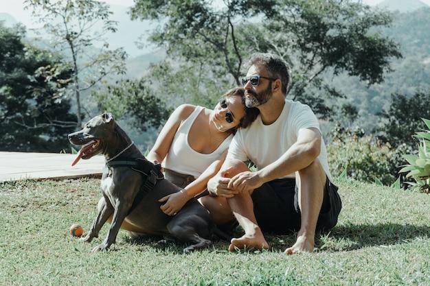 Famille brésilienne formée par homme femme et chien admirant la nature et les montagnes de petropolis