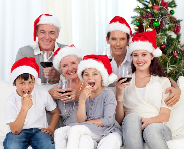 Famille buvant du vin et mangeant des bonbons à noël