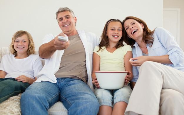 Famille sur le canapé en regardant la télévision ensemble