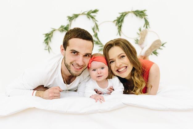 Famille caucasienne de mère, père et bébé souriant à la caméra sur un lit