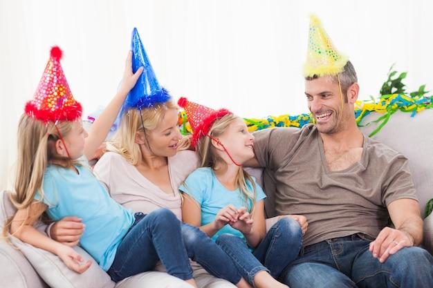 Famille célébrant l'anniversaire de jumeaux assis sur un canapé