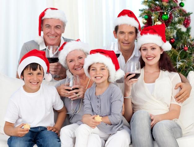 Famille célébrant noël avec du vin et des bonbons