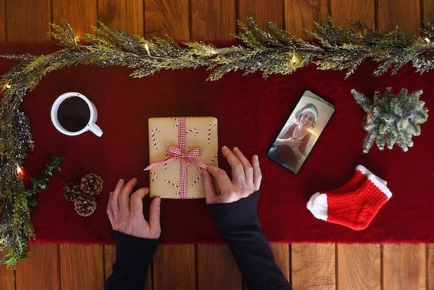 La famille célèbre noël virtuel de loin en communiquant par vidéoconférence et en ouvrant des cadeaux à la maison