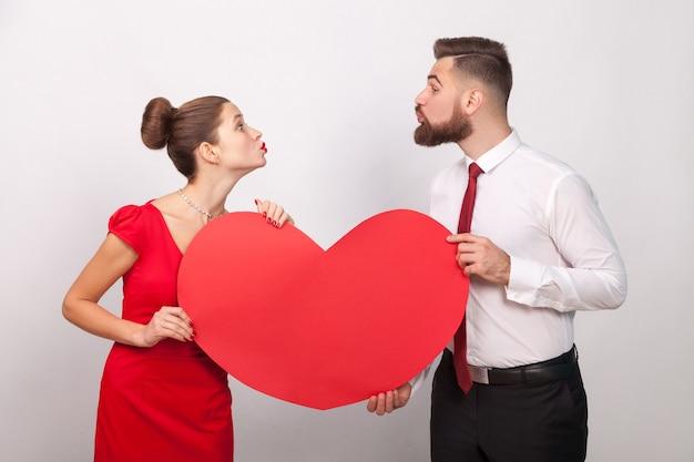 La famille célèbre la saint-valentin en s'envoyant un baiser aérien. intérieur, tourné en studio, isolé sur fond gris