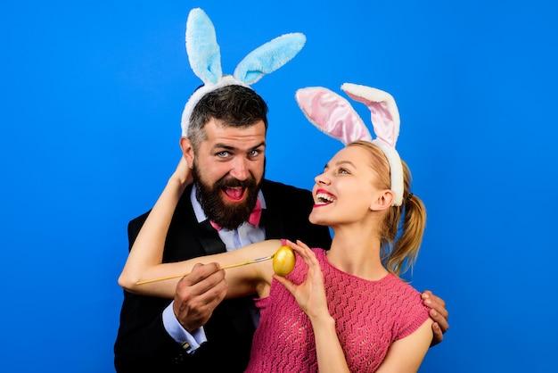 Famille célébrer pâques couple heureux lapin couple joyeuses fêtes couple heureux peignant des œufs pour