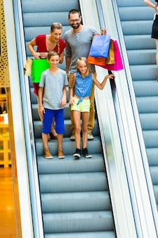 Famille, centre commercial, escalators, sacs