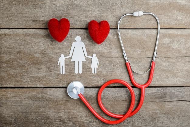 Famille de chaîne de papier coeur rouge, stéthoscope et papier sur une table en bois