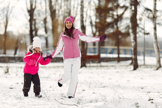 Famille en chapeaux d'hiver tricotés en vacances de noël en famille. femme et petite fille dans un parc. les gens jouent.