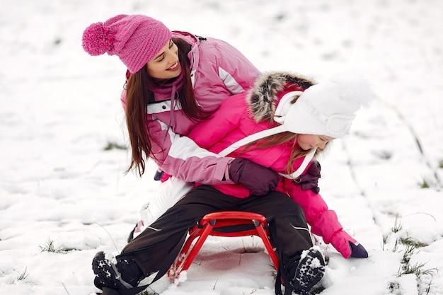 Famille en chapeaux d'hiver tricotés en vacances de noël en famille. femme et petite fille dans un parc. les gens qui jouent avec le traîneau.