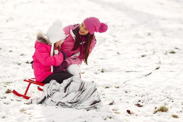 Famille en chapeaux d'hiver tricotés en vacances de noël en famille. femme et petite fille dans un parc. les gens avec thermos.