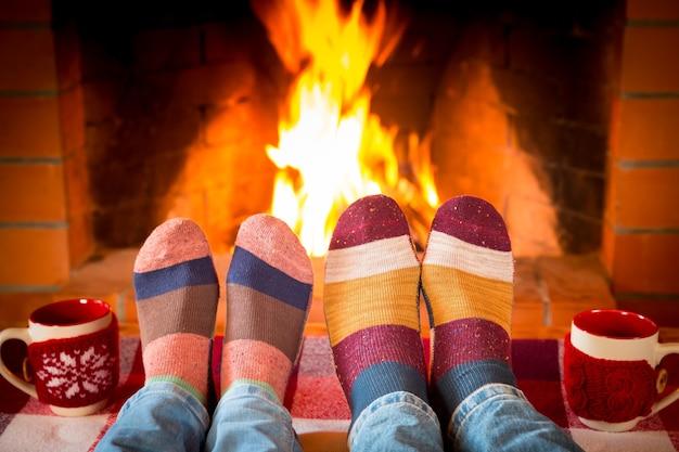 Famille en chaussettes de noël près de la cheminée. mère; père et bébé s'amusant ensemble. les gens se détendent à la maison