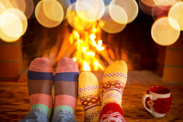 Famille en chaussettes de noël près de la cheminée