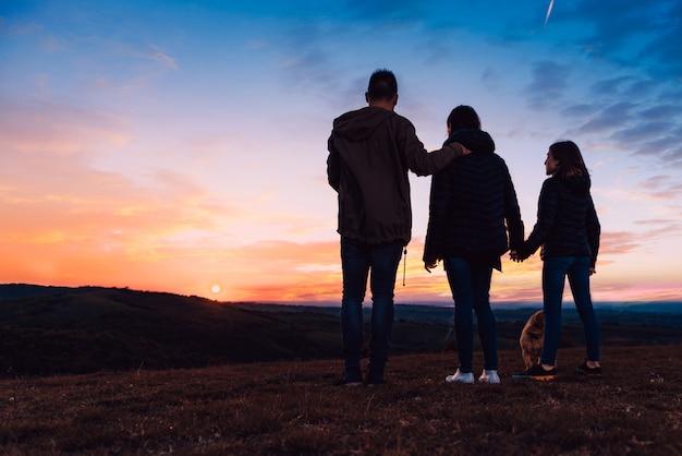 Famille avec chien embrassant debout sur la colline