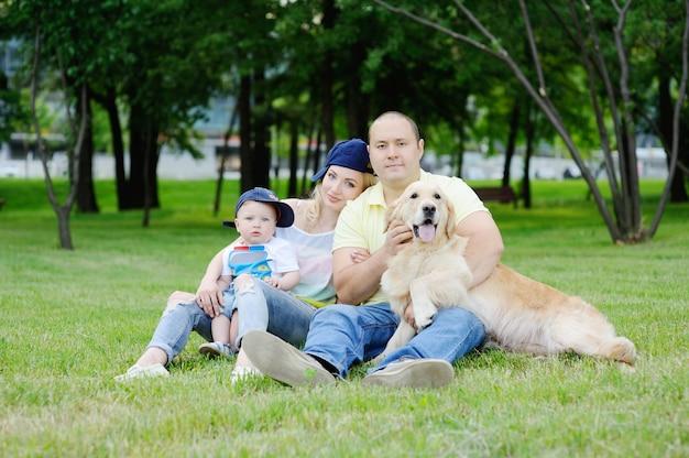 Famille avec un chien golden retriever sur l'herbe