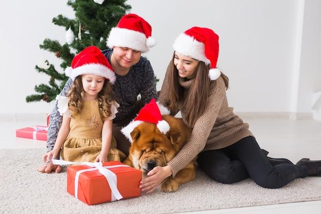 Famille avec chien sont assis sur le sol près de l'arbre de noël