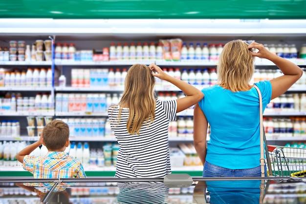 La famille choisit les produits laitiers en boutique