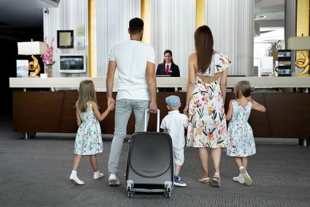 Une famille de cinq personnes entre dans le hall de l'hôtel pour s'enregistrer à la réception pour des vacances.