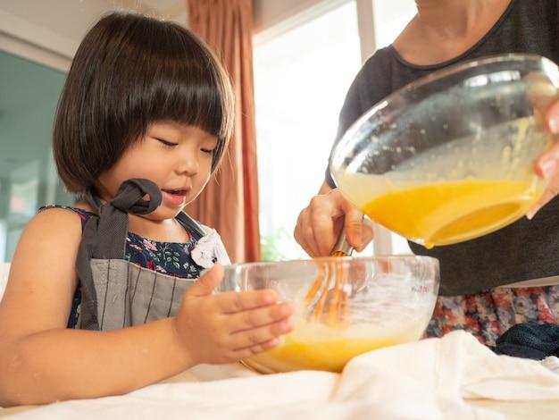 Famille de classe alimentaire dans la salle de cuisine avec son enfant. les asiatiques font des activités ensemble à la maison.