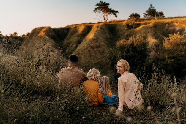 Famille complète assise sur l'herbe ensemble