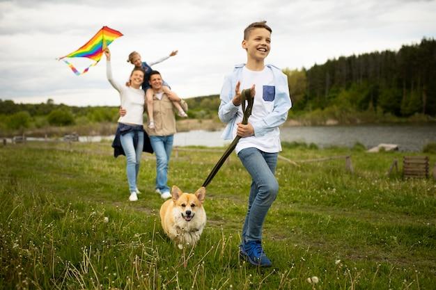 Famille complète jouant avec un cerf-volant à l'extérieur