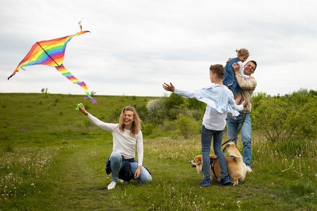 Famille complète jouant avec un cerf-volant