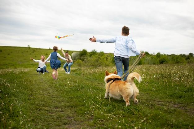 Famille complète jouant avec un chien