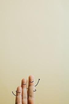 Famille composée de trois doigts sur un fond jaune pastel avec espace de copie