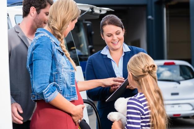 Famille conseillée par un vendeur achetant une voiture