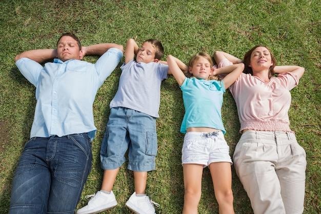 Famille de couchage allongé sur l'herbe dans une rangée