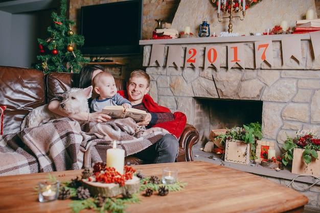 Famille couché sur un canapé avec une couverture pendant qu'ils lisent un livre et une cheminée en arrière-plan