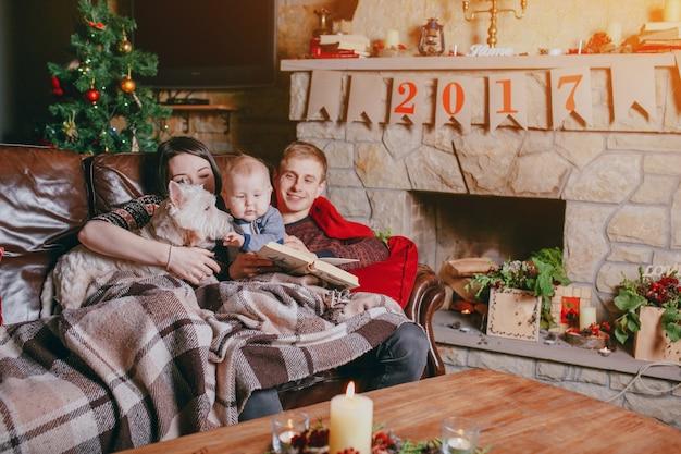 Famille couché sur le canapé recouvert d'une couverture pendant qu'ils regardent un livre et sur la table il y a une bougie allumée