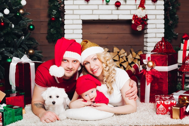 Famille, coucher plancher, près, cheminée, petit fils, chien, sourire, à, caméra