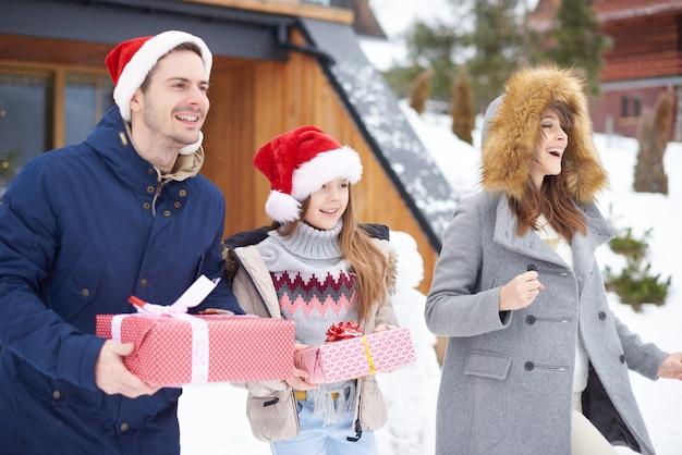 Famille en cours d'exécution avec des cadeaux de noël