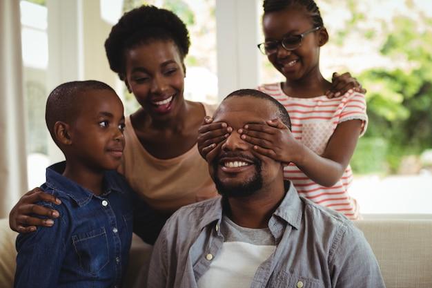 Famille couvrant les yeux de l'homme pour la surprise