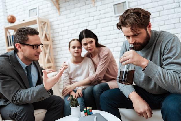 Famille dans un bureau de psychologue problèmes d'alcoolisme.