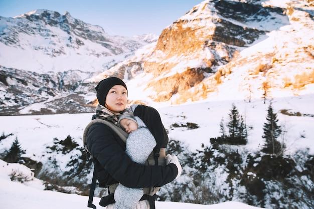 Famille dans la campagne enneigée d'hiver avec la montagne en arrière-plan randonnée hivernale en montagne en autriche