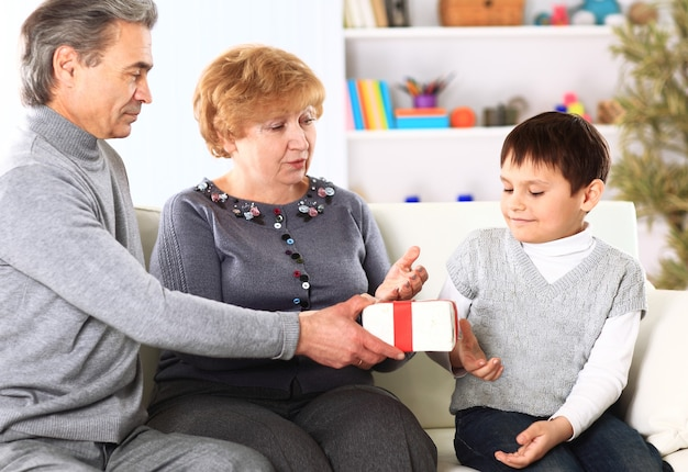 Famille dans un canapé donnant des cadeaux pour noël